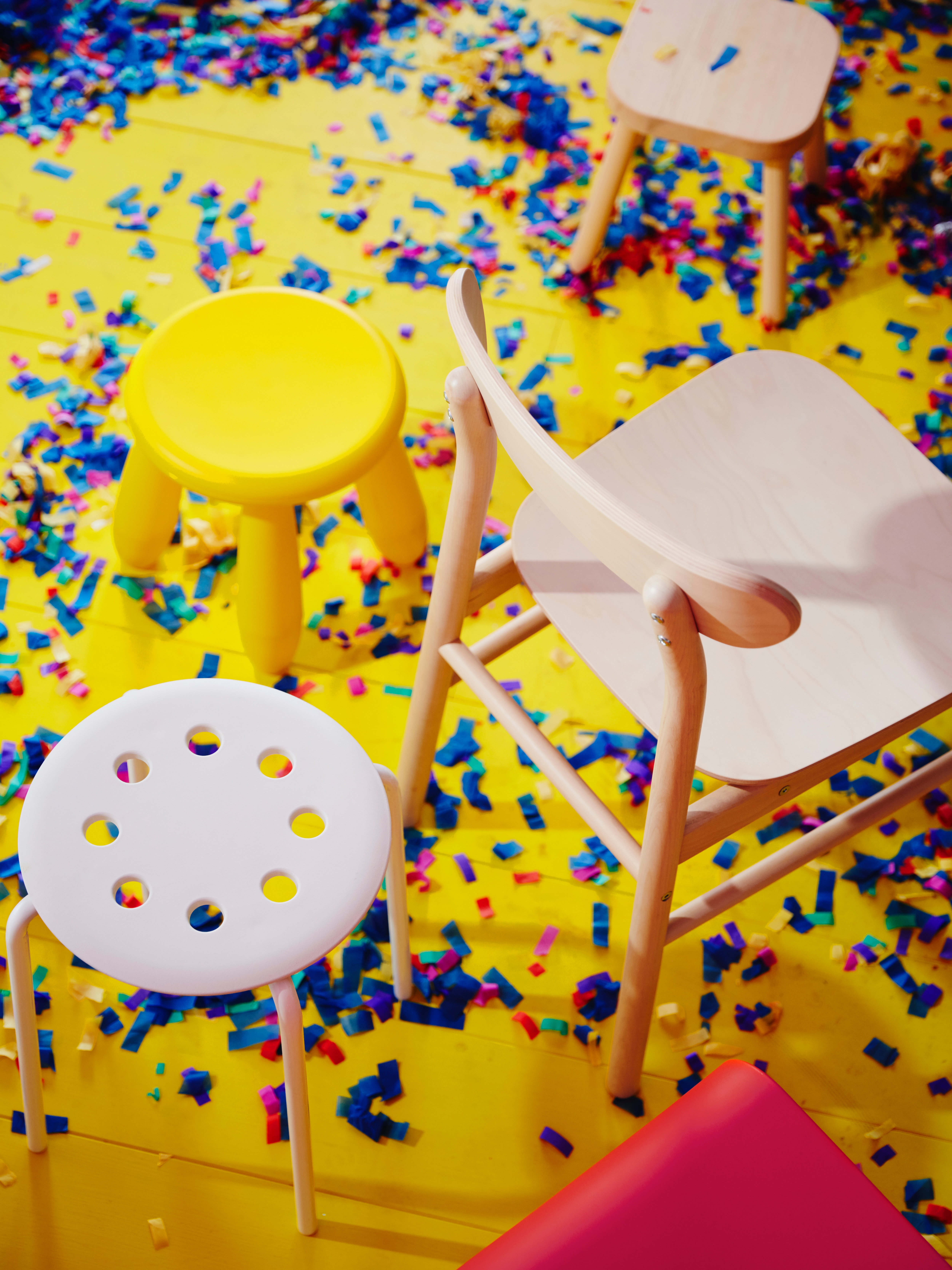 An aerial view of a confetti-covered floor with different stools and a solid birch RÖNNINGE chair that has a curved backrest.