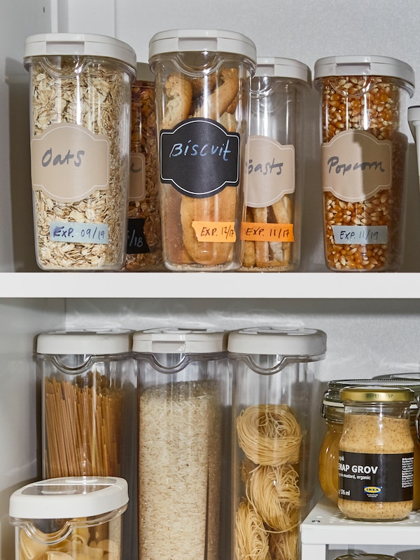 A close-up of shelves with 365+ dry food jars with lids storing oats, biscuits, popcorn and cereals.