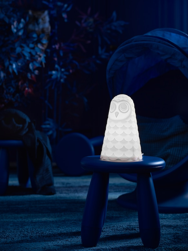 A lit SOLBO LED table lamp sits on a MAMMUT stool in the dark in the middle of the floor in a child's room.