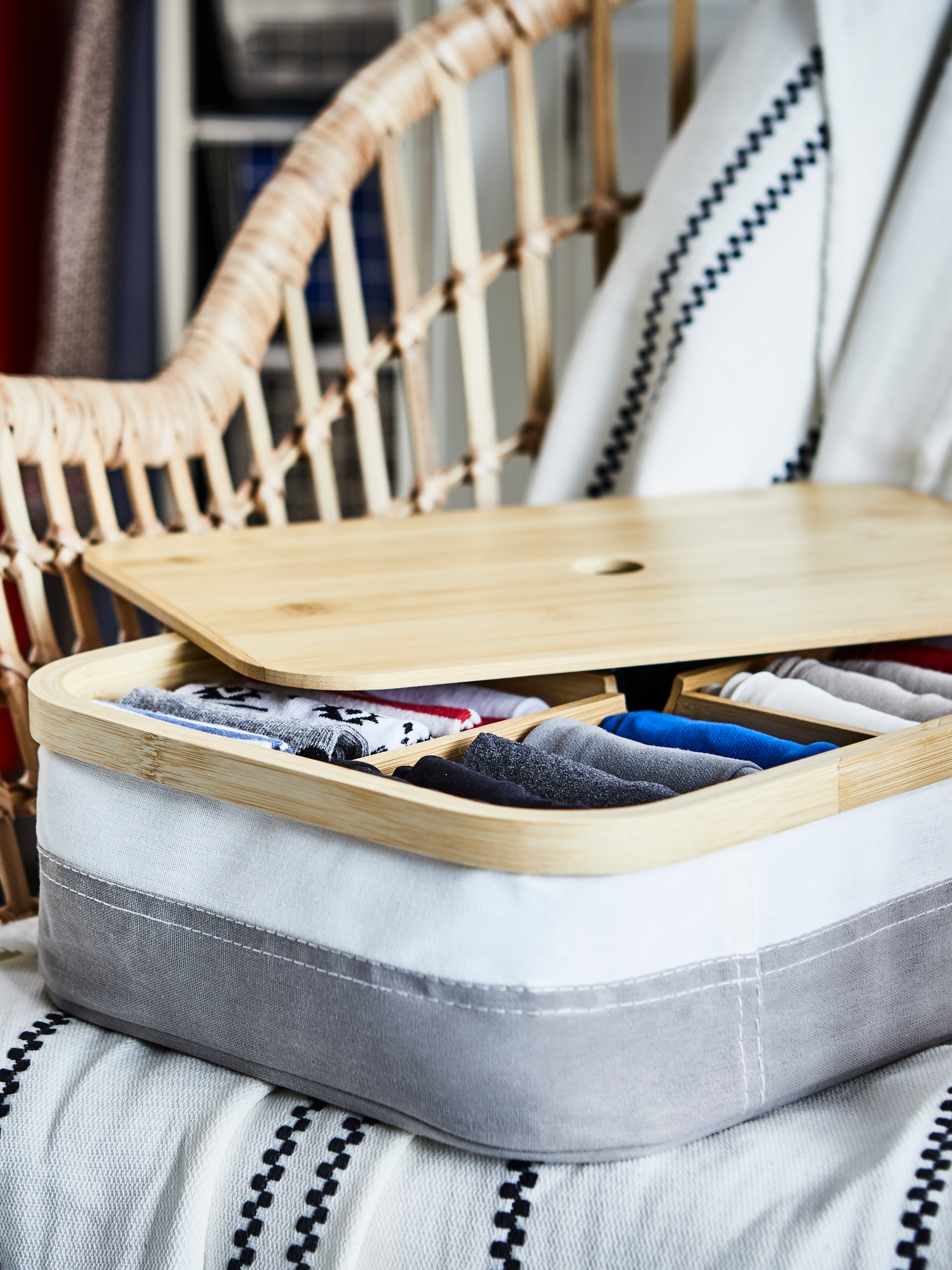 RABBLA kutija s odjeljcima i drvenim poklopcem na pletenoj stolici, u kojoj je i pamučni konac i razni drugi predmeti za šivanje.