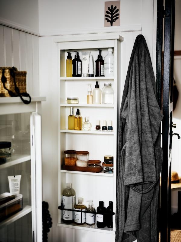 Le coin d'une salle de bain blanche avec une étagère murale HEMNES sur un mur. Des produits de soin et accessoires de bain sont rangés sur les tablettes.