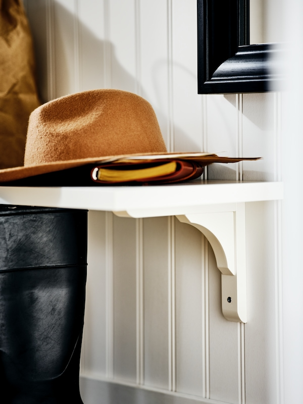 L'extrémité d'une étagère murale BERGSHULT/RAMSHULT blanche, sur un mur avec soubassement en lambris de bois. Un chapeau brun et un carnet sont posés dessus.