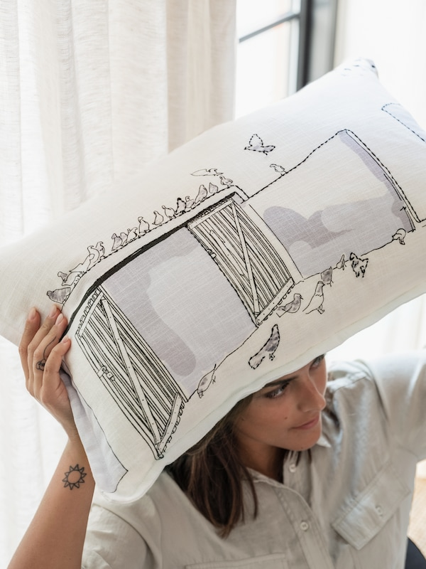 手刺繍で仕上げたクッションを持ち上げる女性。アンマンの屋上にいるハトの群れが見える。