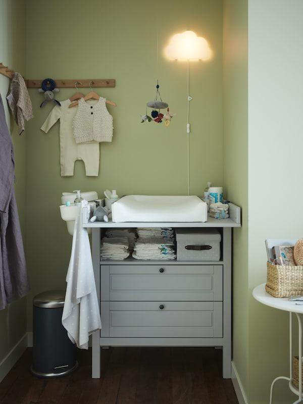 Gråt puslebord/kommode, knagerækker af eg, hvor der hænger babytøj, en puslepude og en hvid LED-væglampe formet som en sky.