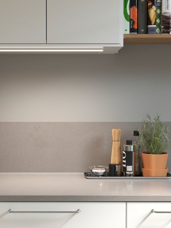 A light grey laminate kitchen backsplash with a mineral effect and a matching worktop below a wall-mounted cabinet.