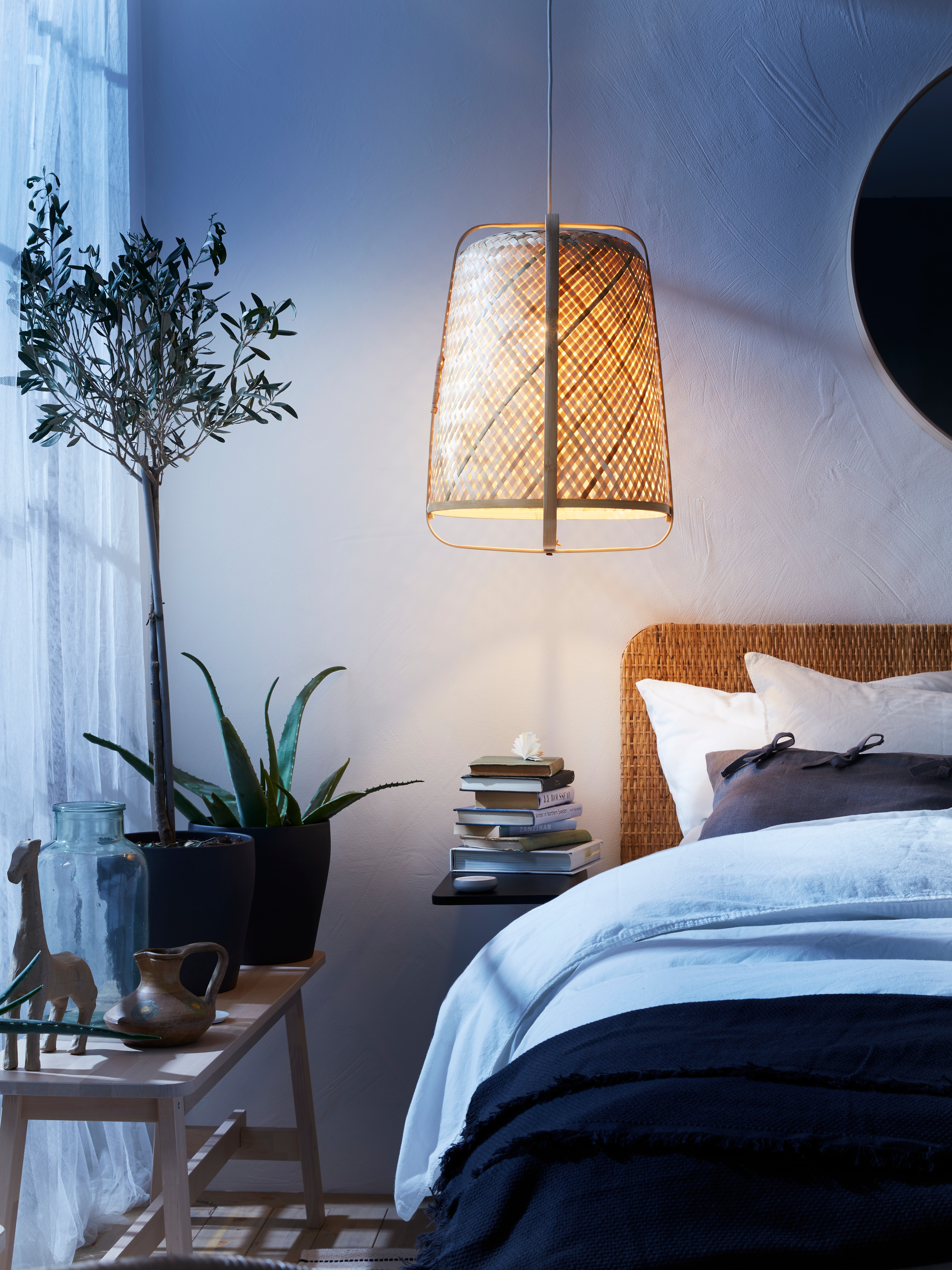 An illuminated, bamboo KNIXHULT pendant lamp that's handwoven and bell shaped, hanging above a bed with a rattan headboard.