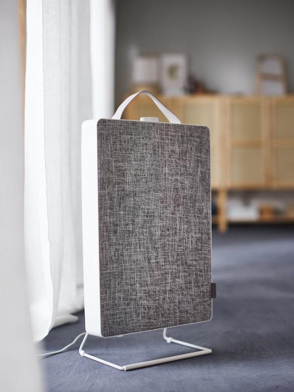 햇살이 비치는 화이트 커튼 앞에 놓여 있는 화이트 FÖRNUFTIG 푀르누프티그 공기청정기