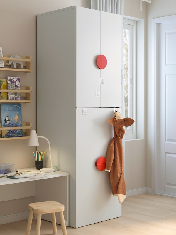 A white SMÅSTAD wardrobe with pull-out unit in a child's room by a white desk with FLISAT wall storage above holding books.