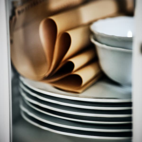 Une pile d'assiettes UPPLAGA blanches avec tout en haut deux bols UPPLAGA, ainsi que quelques serviettes brun clair.