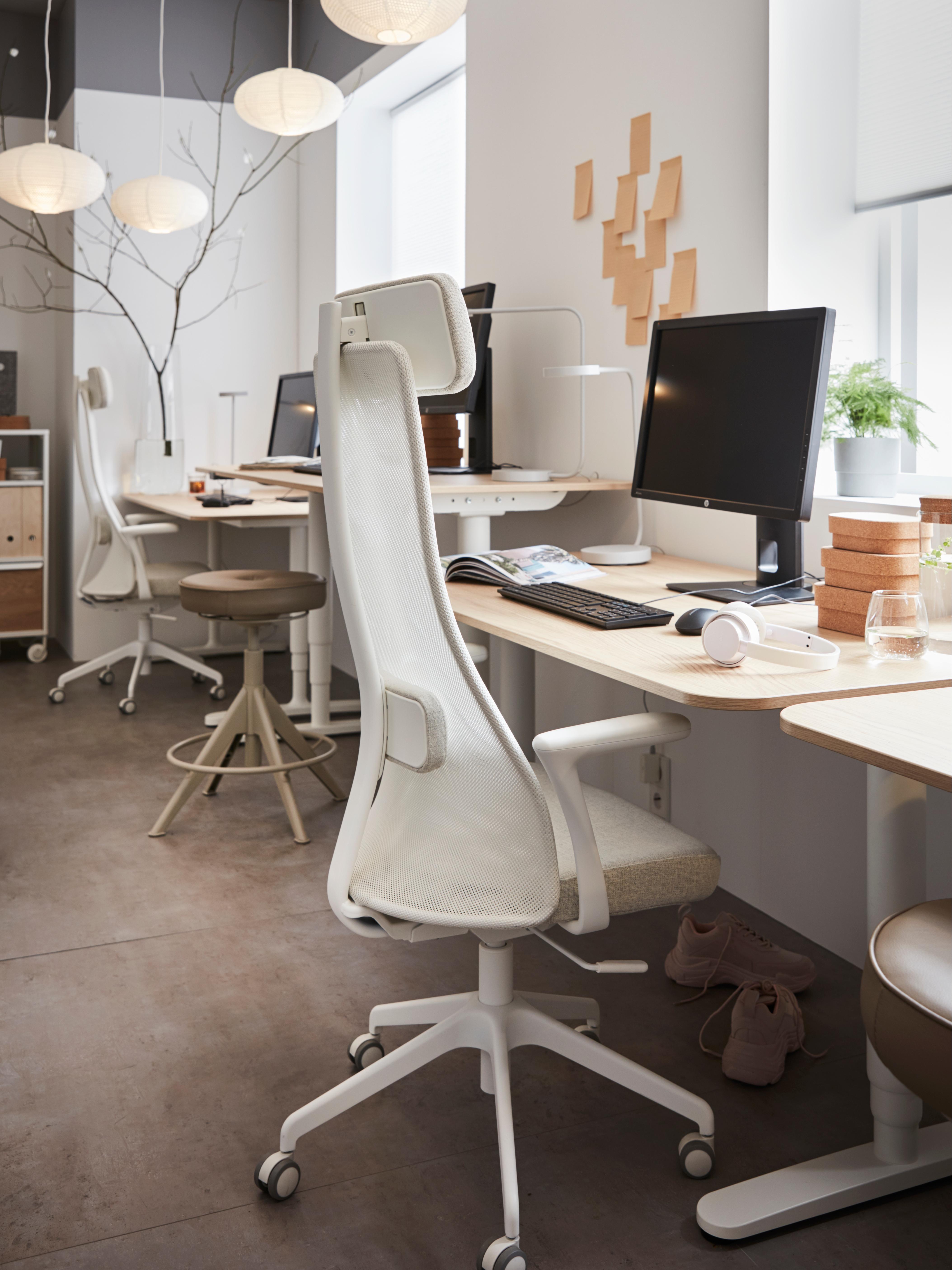 Sedia da ufficio alta JÄRVFJÄLLET beige e bianca con braccioli e rotelle, vicino a scrivanie di varie altezze.