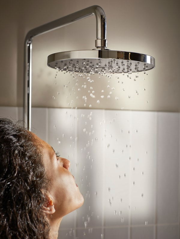 Senhora em baixo de um chuveiro redondo a pingar água.