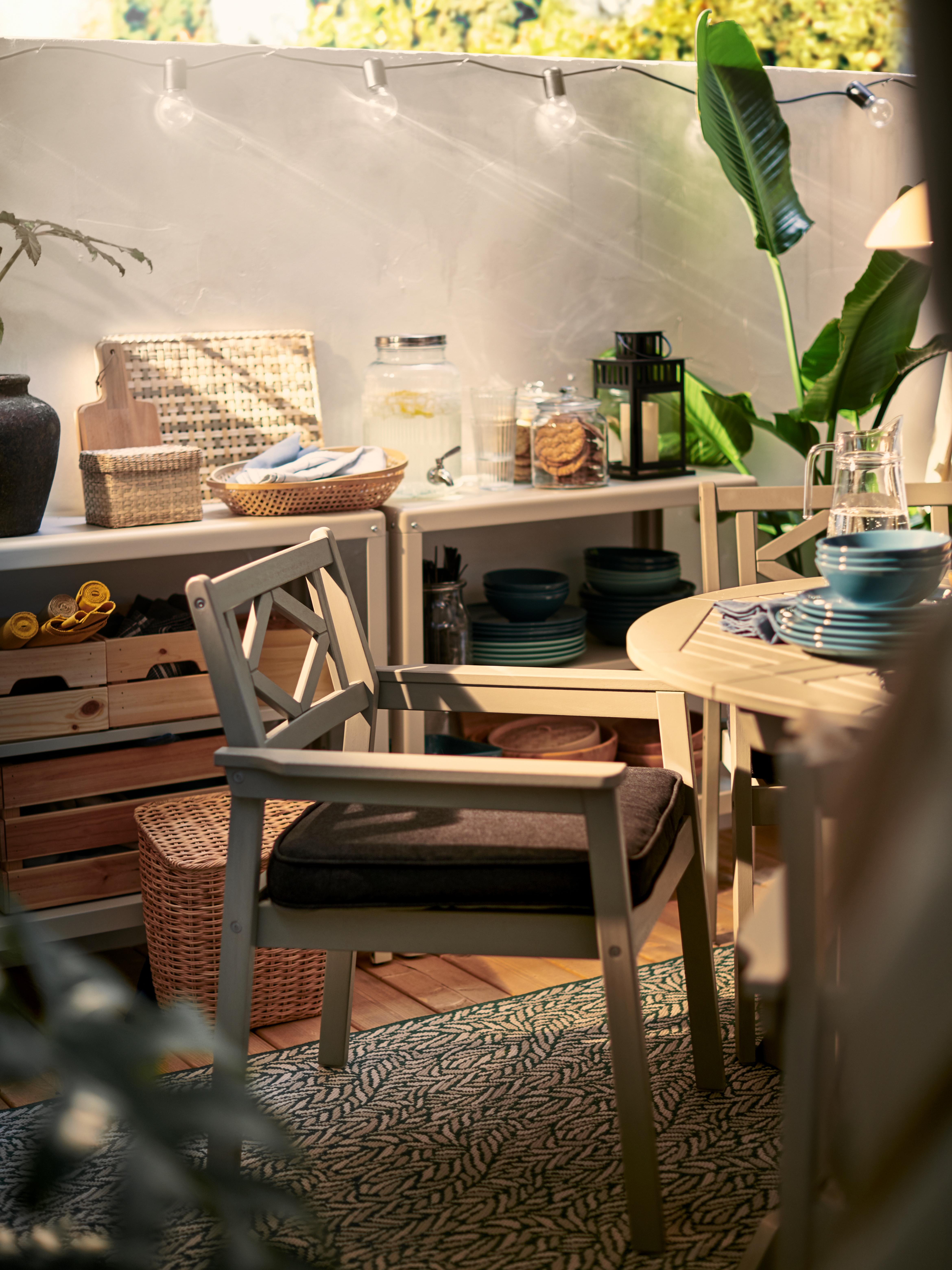 Une chaise d'extérieur BONDHOLMEN grise avec un coussin noir crée une assise confortable pour une table de salle à manger en plein air.