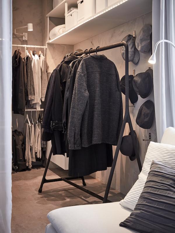 Wintermäntel und Jacken hängen hier an einem schwarzen TURBO Kleiderständer, der an der Wand eines Schlafzimmers steht.