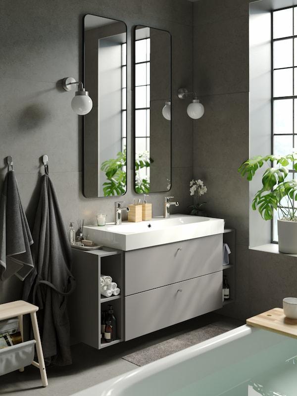 Un meuble lavabo GODMORGON/BRÅVIKEN gris foncé avec deux tiroirs, deux étagères de part et d'autre, et deux miroirs au-dessus du lavabo.