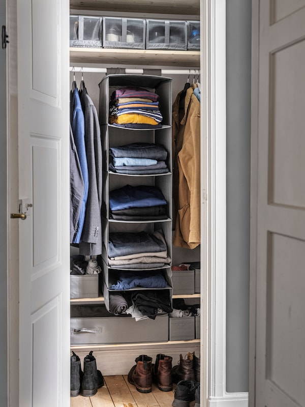 Hanging SKUBB storage with 6 compartments inside a wardrobe filled with clothes.