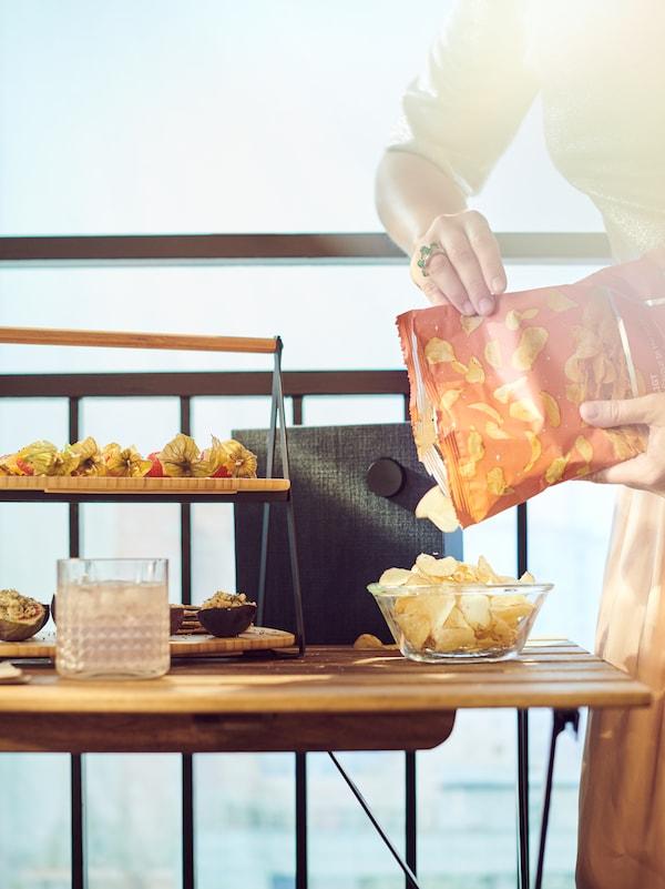 Kobieta napełniająca chipsami ziemniaczanymi FESTLIGT miskę ustawioną na stoliku balkonowym, na którym stoją też taca do serwowania FULLSPÄCKAD i głośnik Bluetooth.