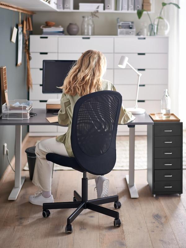 Una donna seduta su una sedia da ufficio FLINTAN nera davanti a una scrivania regolabile in altezza RODULF grigia con sopra un computer e una lampada da lavoro, accanto a una cassettiera - IKEA