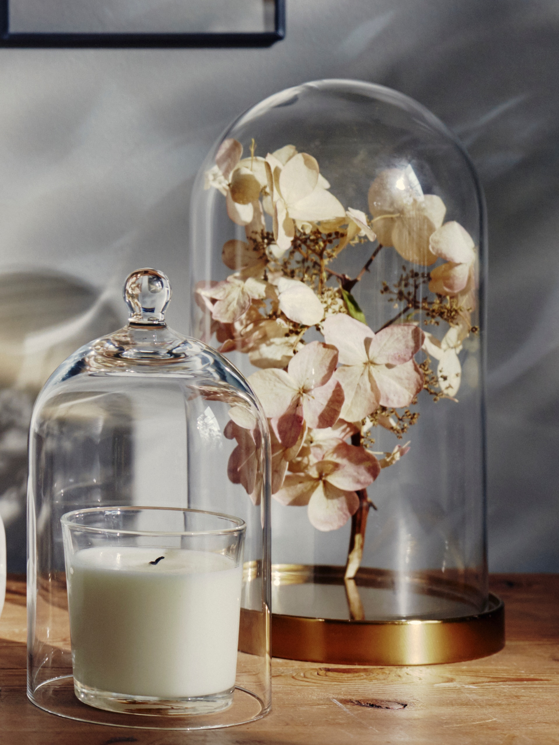 A BEGÅVNING glass dome with base holds a spring of dried flowers by another glass dome covering an unlit candle on a table.