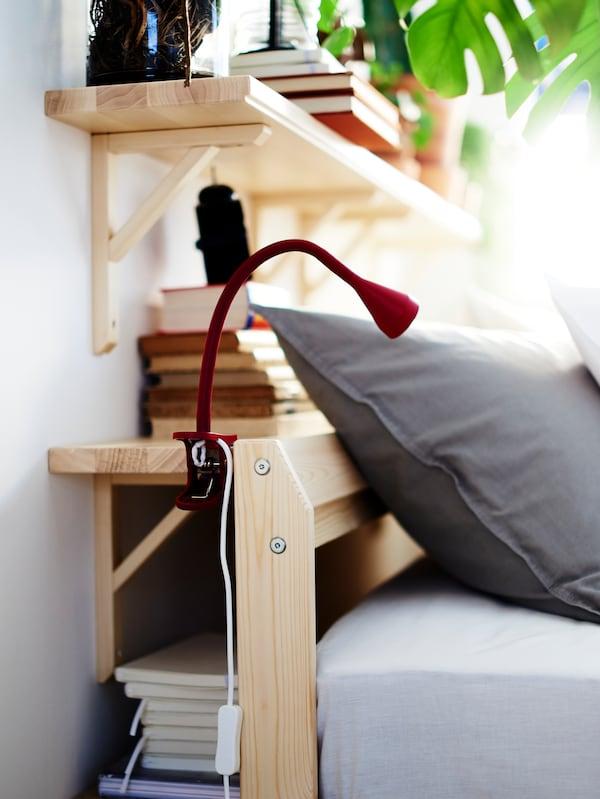 Un pat NEIDEN din pin stă lângă două polițe de perete TRANHULT/SANDSHULT care sunt montate pe un perete de dormitor.