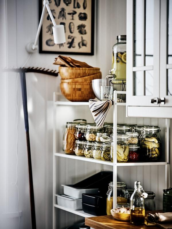 Une étagère JONAXEL blanche dans laquelle sont rangés des bocaux de légumes en conserve, des plats et des saladiers en verre, à côté d'une armoire murale.