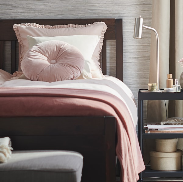 Postel IDAN namořená na tmavě hnědou barvu v ložnici vedle černého  stolku KORNSJÖ s lampou.