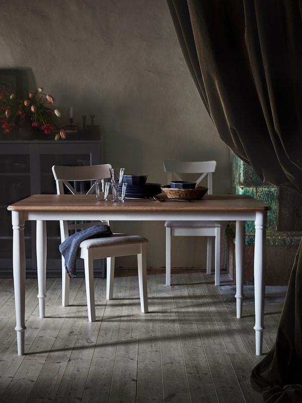 Ein DANDERYD Esstisch mit zwei Stühlen dahinter steht in einem Raum mit einer großen braunen Gardine auf einer Seite und einem Holzfußboden.