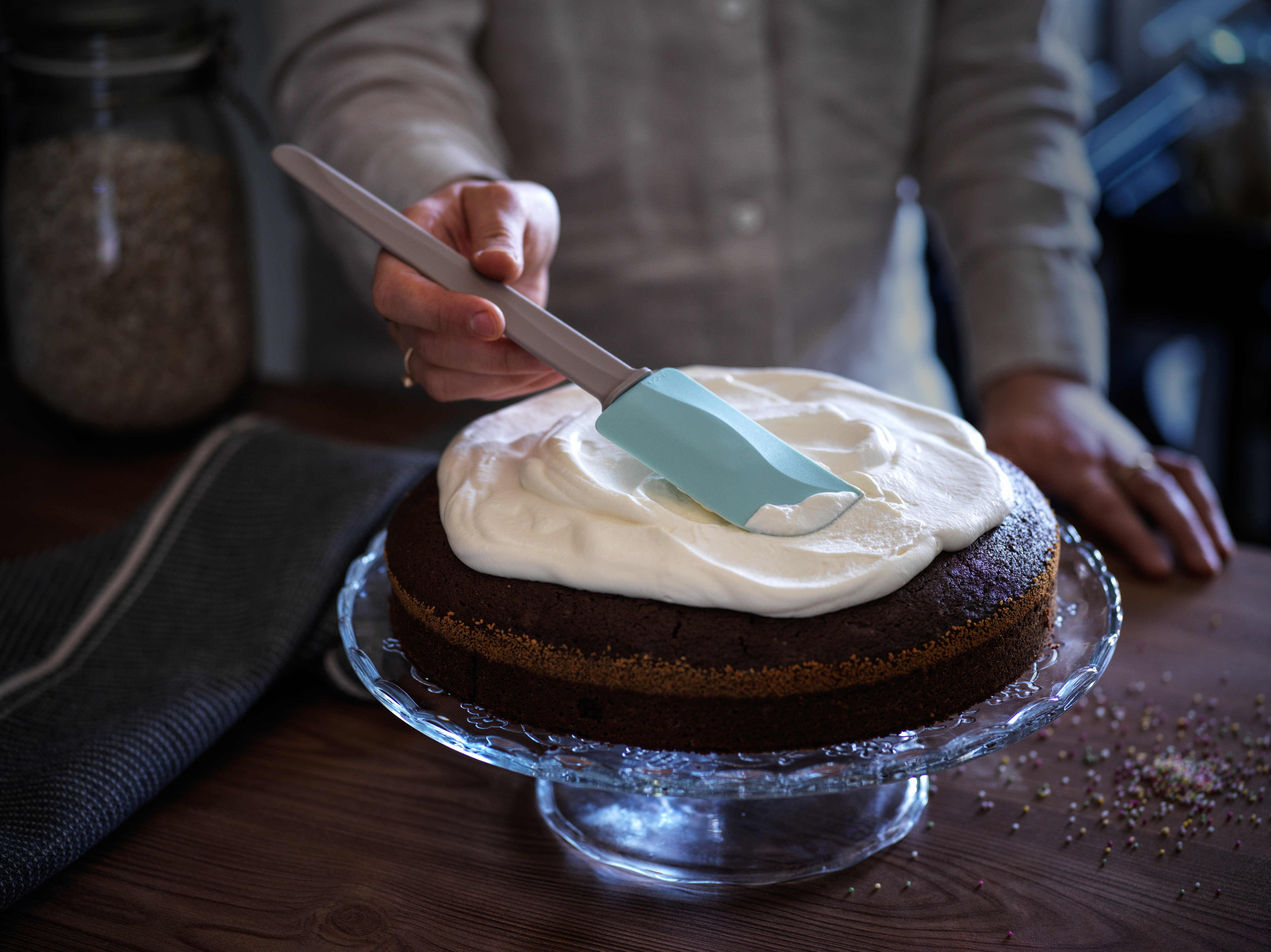 Baker uses rubber spatula to frost a cake on glass cake stand