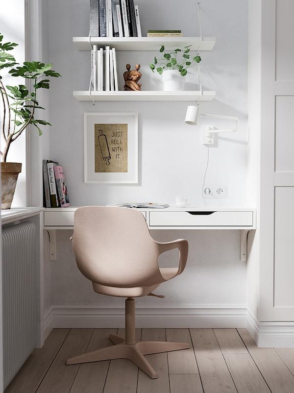 Vaalea huone, jonka nurkassa ikkunan edessä on pieni työpiste. Pöytä on rakennettu EKBY ALEX -hyllystä ja tuolina on beige ODGER-työtuoli. Pöydän päällä on seinään kiinnitettynä NYMÅNE-seinävalaisin sekä kaksi valkoista BERGSHULT-seinähyllyä.