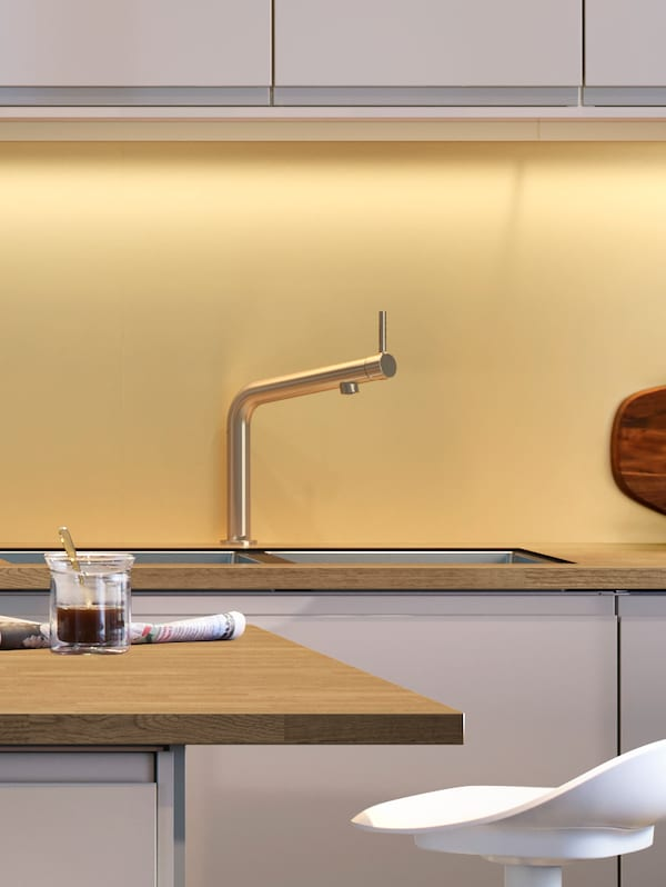 A kitchen with a yellow wall panel, a stainless steel faucet and a wooden countertop with a kitchen island in front.