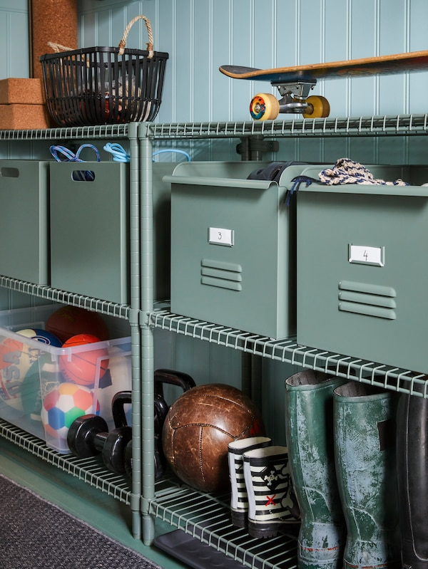 Close-up of green shelving unit with metal organizers with scarves stored. Boots on lower shelf.