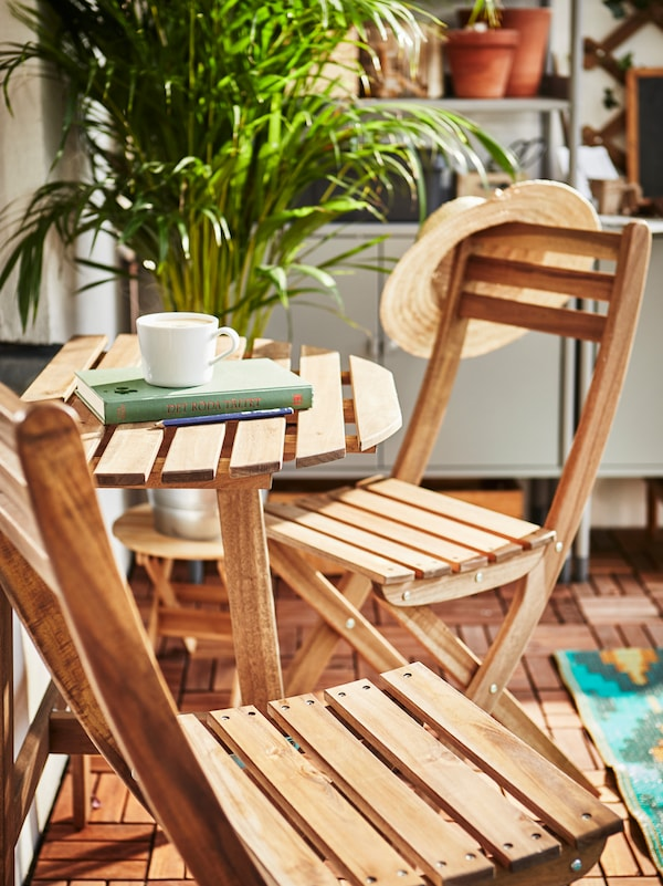 Two wooden chairs and a wooden outdoor table holding a cup and a book, a hat hanging on one chair, and a potted plant.