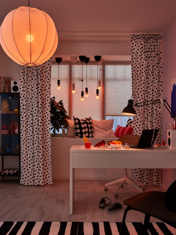 TRÅDFRI LED smart light bulbs in the ceiling lamp, window lamps and desk lamp cast an orange glow in a home office.