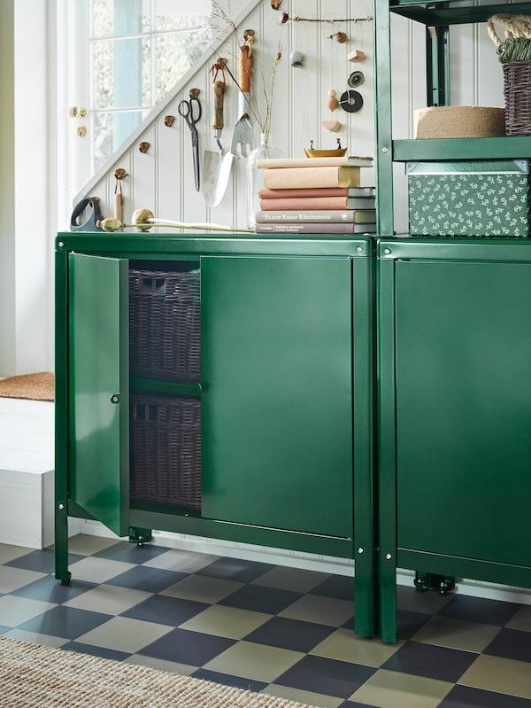 Två gröna KOLBJÖRN skåp står intill en trappa. Ena skåpdörren är öppen och inuti syns mörkbruna rottingkorgar.