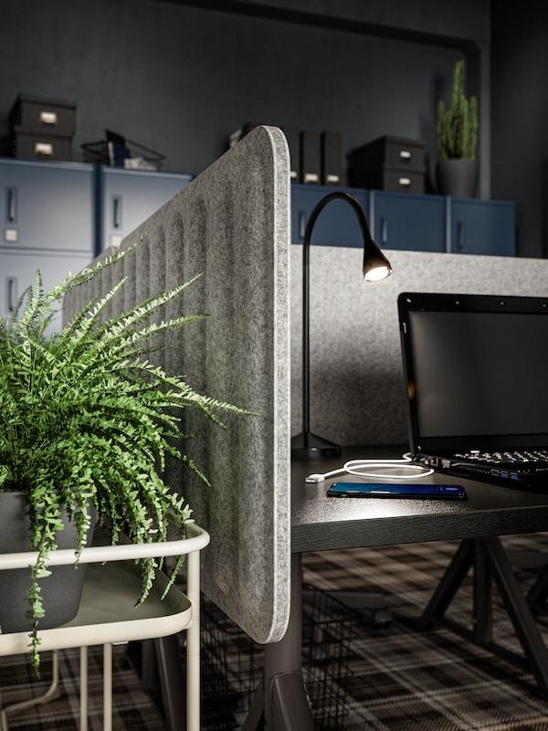Paravento in feltro grigio su una scrivania, lampada da lettura nera, PC portatile nero e una pianta su un piedistallo per piante beige.