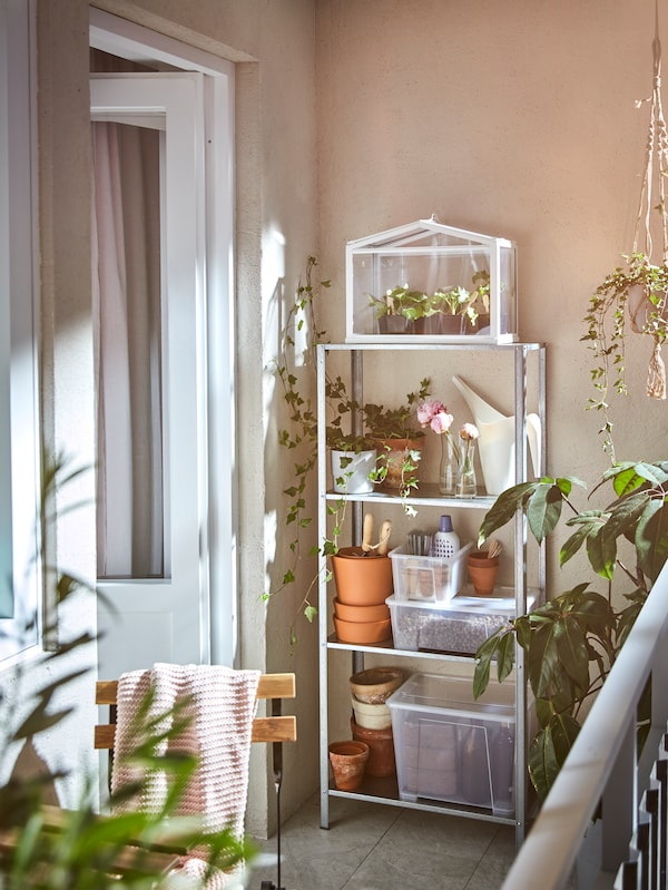 The HYLLIS shelf against a wall on a balcony full of plants, plant pots, storage bins and watering cans.