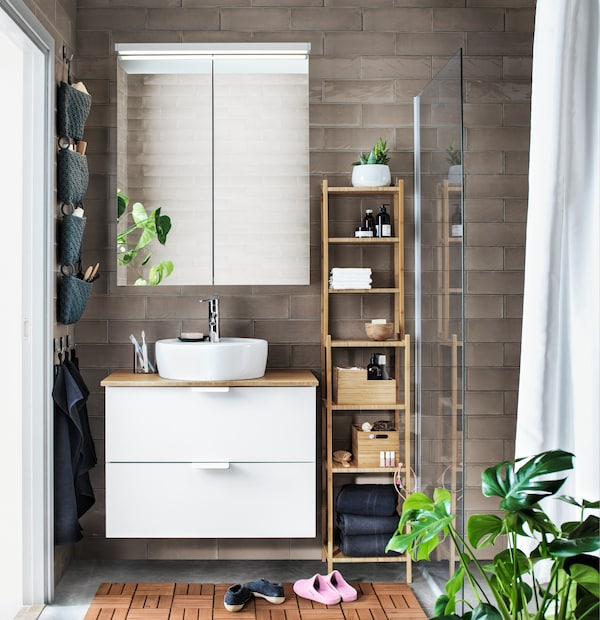 A bathroom with white and bamboo furniture, a mirrored cabinet, and plants.