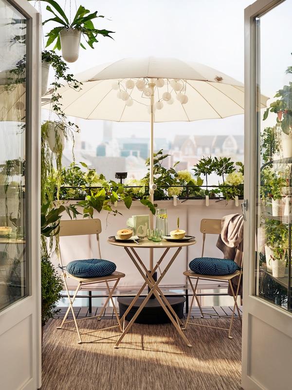 Ein Balkon mit zwei Stühlen mit Sitzkissen und einem Klapptisch, auf dem Teller mit Melonenhälften, Gläser und andere Gegenstände stehen.