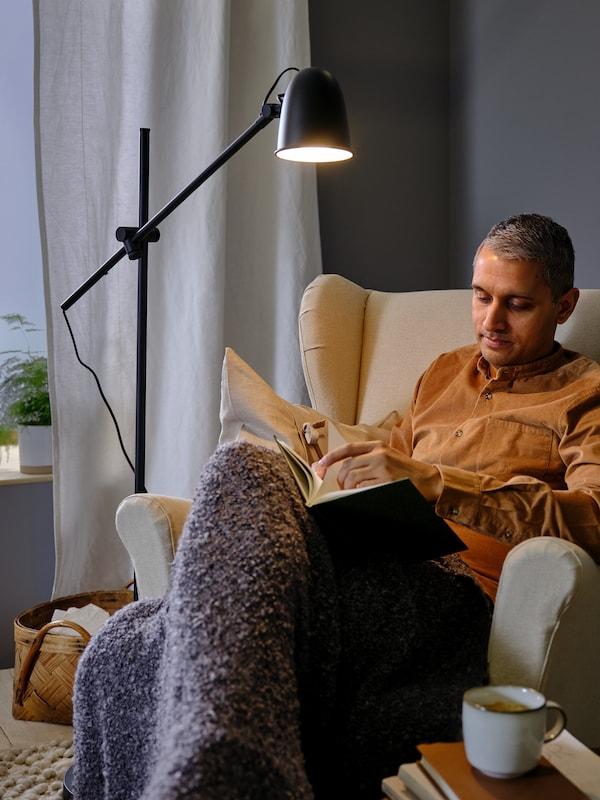 Eine Person sitzt beim Licht einer SKURUP Standleuchte in einem STRANDMON Ohrensessel und liest in einem Buch.