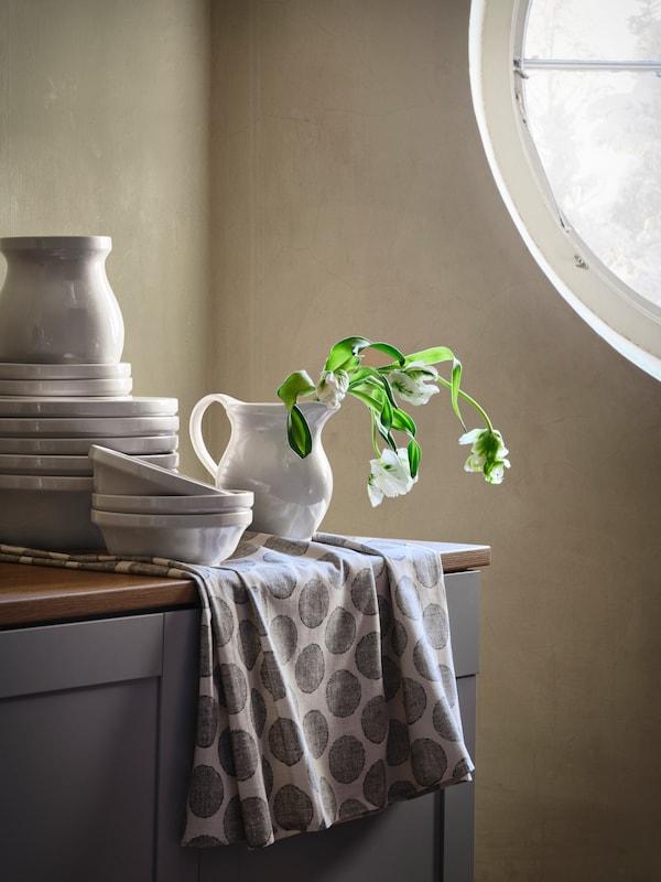 Les bols, vases et pichets DEKORERA blancs sont empilés les uns sur les autres sur un buffet de cuisine, avec des fleurs dans un pichet.