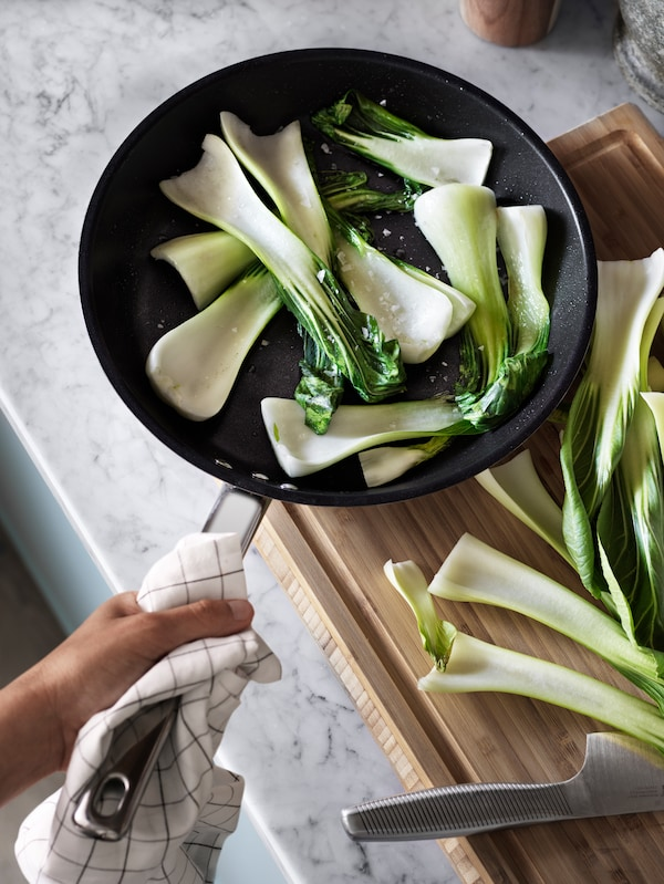 A person holding a frying pan with a towel around the stainless-steel handle fries pak choi next to a wooden chopping board.