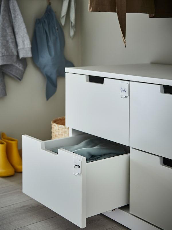 Une commode NORDLI avec des étiquettes sur les tiroirs, dont l'un est ouvert. Derrière, on voit des chaussures d'enfants et des sacs suspendus.