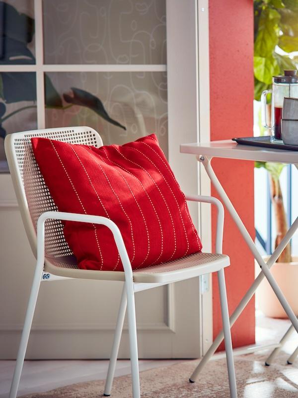 Conjunto de mesa y silla de comedor TORPARÖ junto a la puerta abierta de un balcón. En la silla hay un cojín con una funda roja FESTHOLMEN.