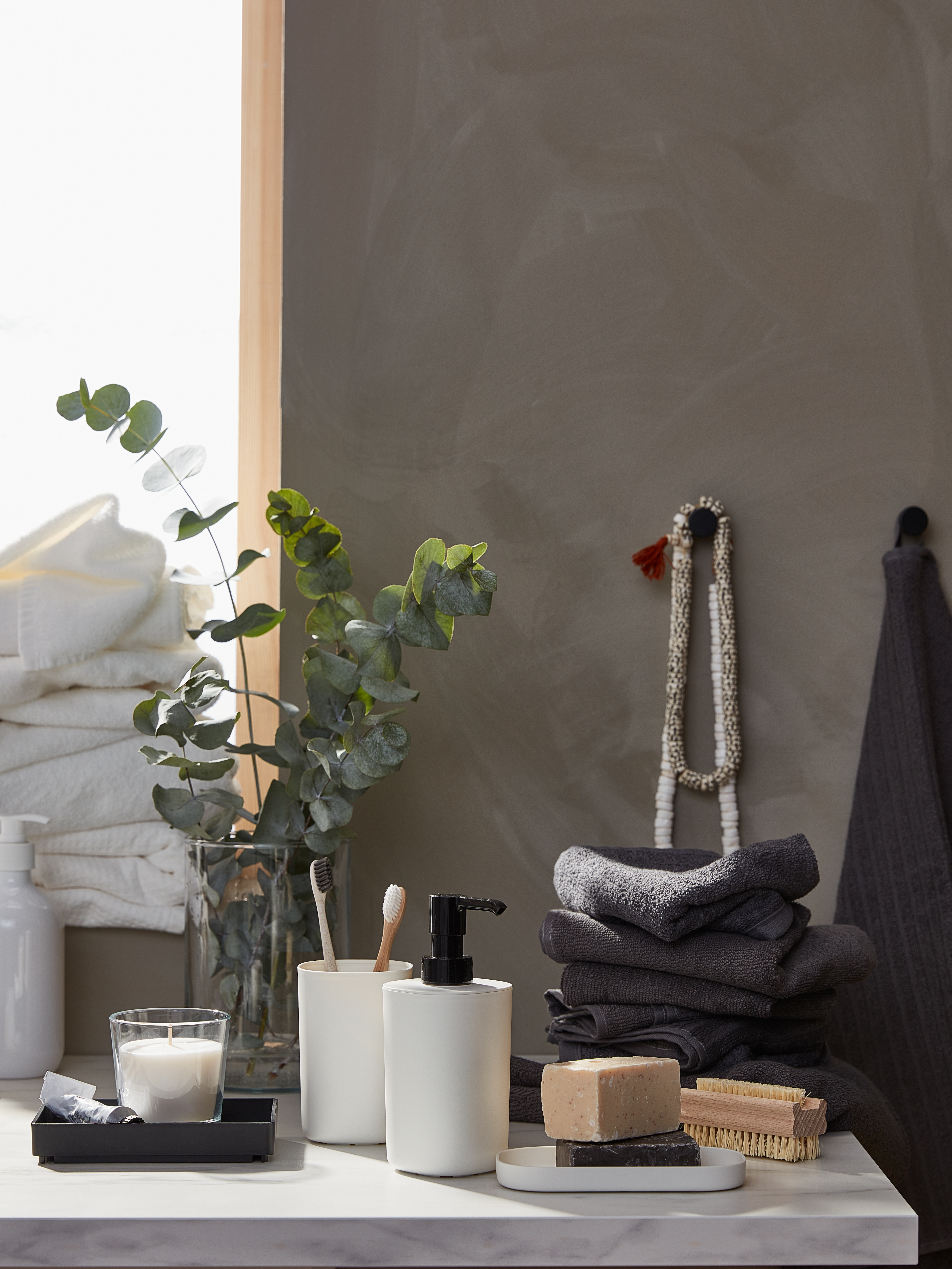 A surface with a white STORAVAN bathroom set, stacked, dark-grey VÅGSJÖN towels and decorative bathroom accessories.
