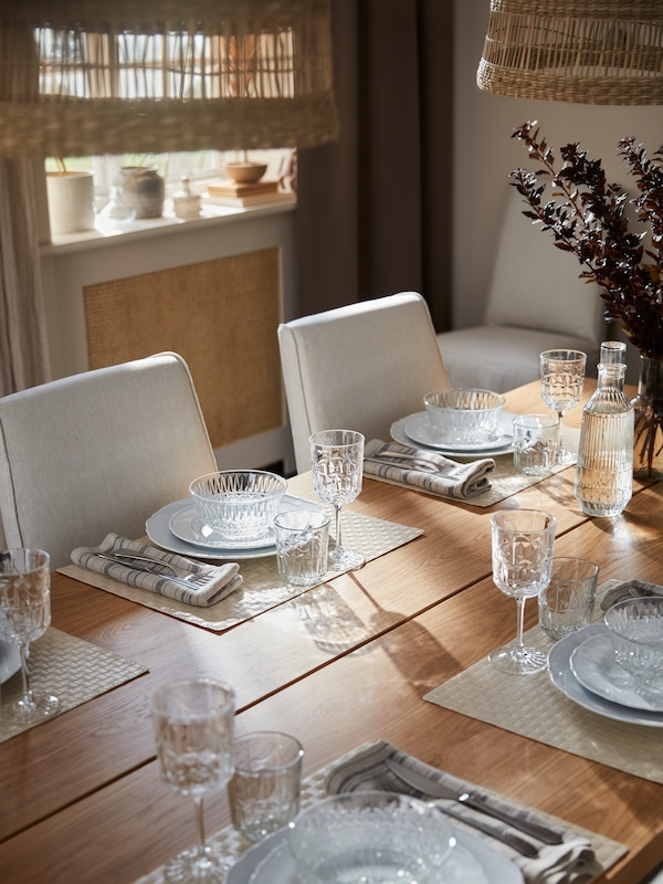 A MÖCKELBY table set for dinner with tableware and table linen including UPPLAGA plates and SÄLLSKAPLIG wine glasses.