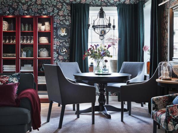 Chambre colorée avec des motifs et des matériaux mélangés.  Une table à manger ronde et des chaises avec accoudoirs se trouvent sur le côté de la pièce, près des fenêtres. Une vitrine de rangement rouge est située sur le mur du fond.