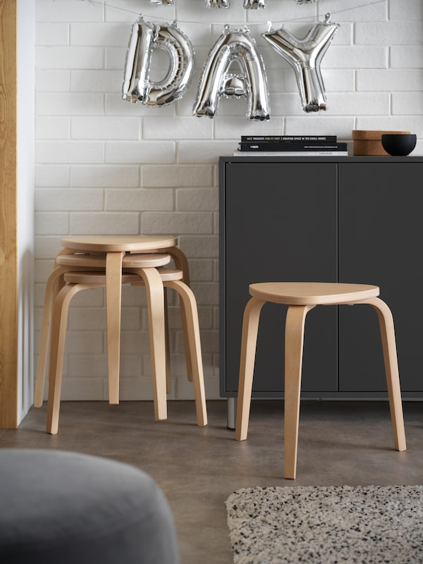 Four KYRRE stools in birch next to a dark-grey EKET cabinet with doors, in front of a white wall in a living room.
