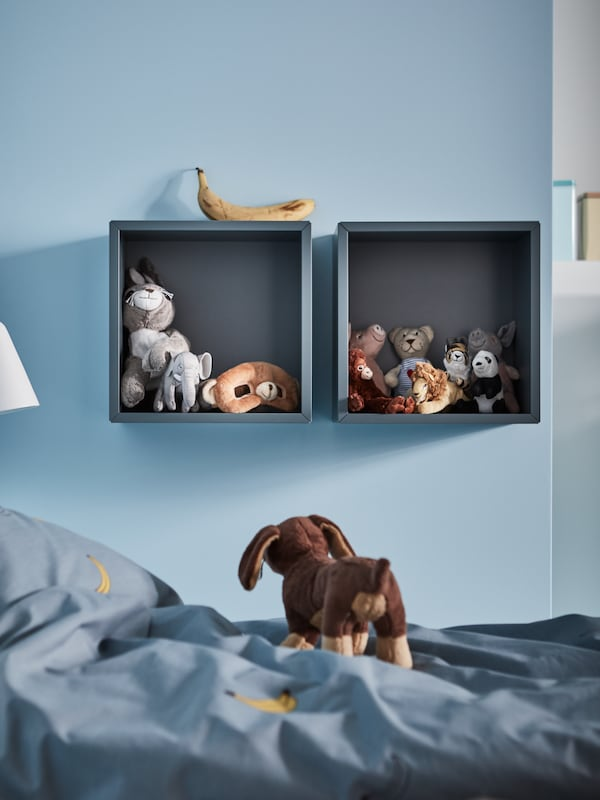A children's bedroom with two grey-turquoise EKET cabinets filled with toys and a blue quilt cover with a banana pattern.