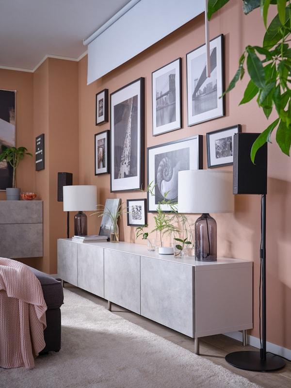 Una combinación de almacenaje BESTÅ baja en blanco con armarios abiertos y puertas LAPPVIKEN con un televisor encima. Delante hay una alfombra MORUM en gris oscuro.