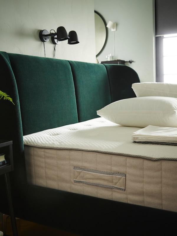Čalouněná postel TUFJÖRD postavená u zdi, na posteli je matrace VATNESTRÖM, polštáře a ložní prádlo.
