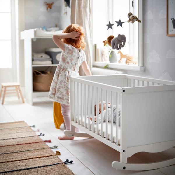 In a children's room, a child stands near a SOLGUL cradle with foam mattress in which a baby lies on its back.
